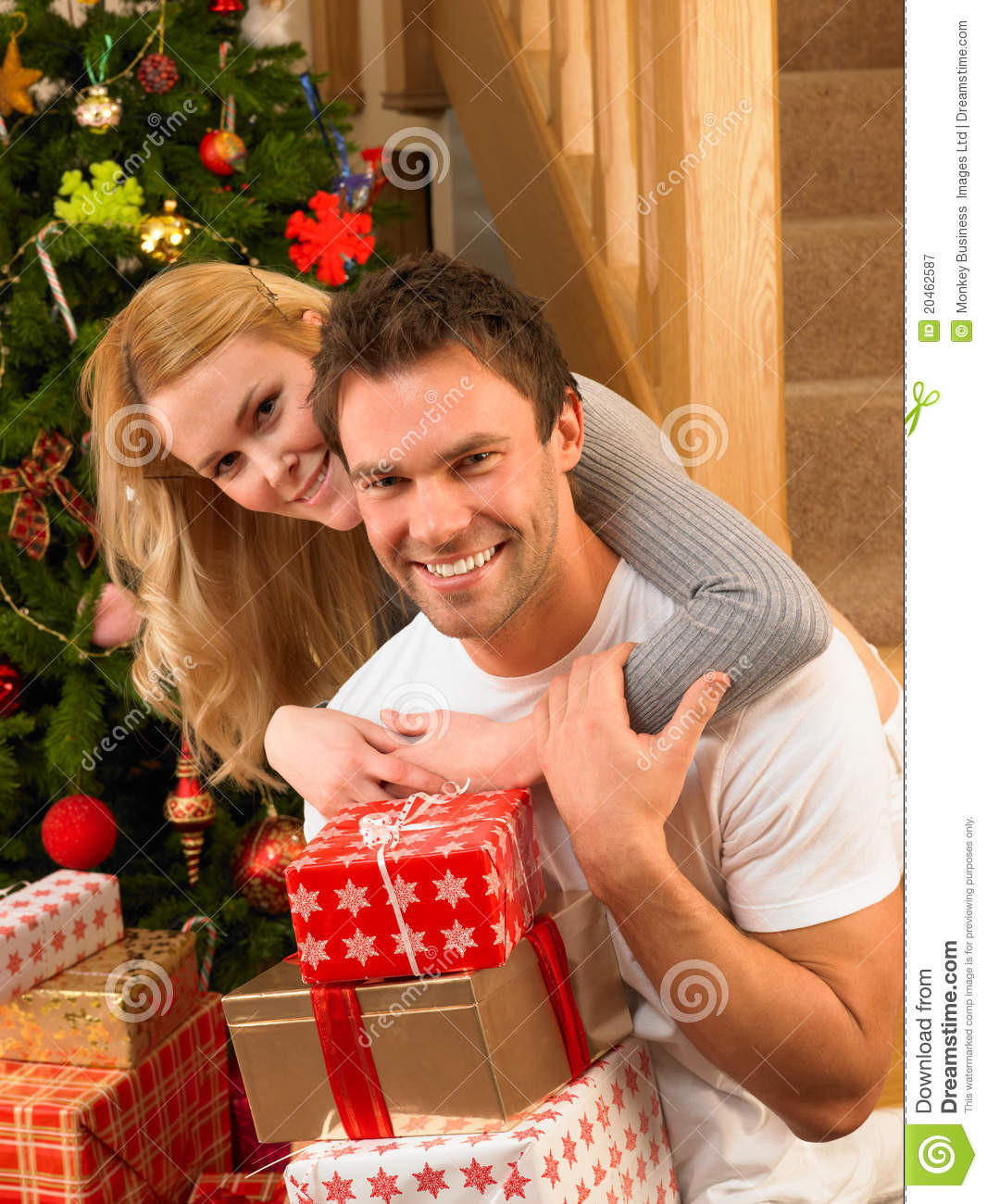 Best ideas about Christmas Gift Ideas For Young Couples . Save or Pin Young Couple At Christmas Exchanging Gifts Royalty Free Now.