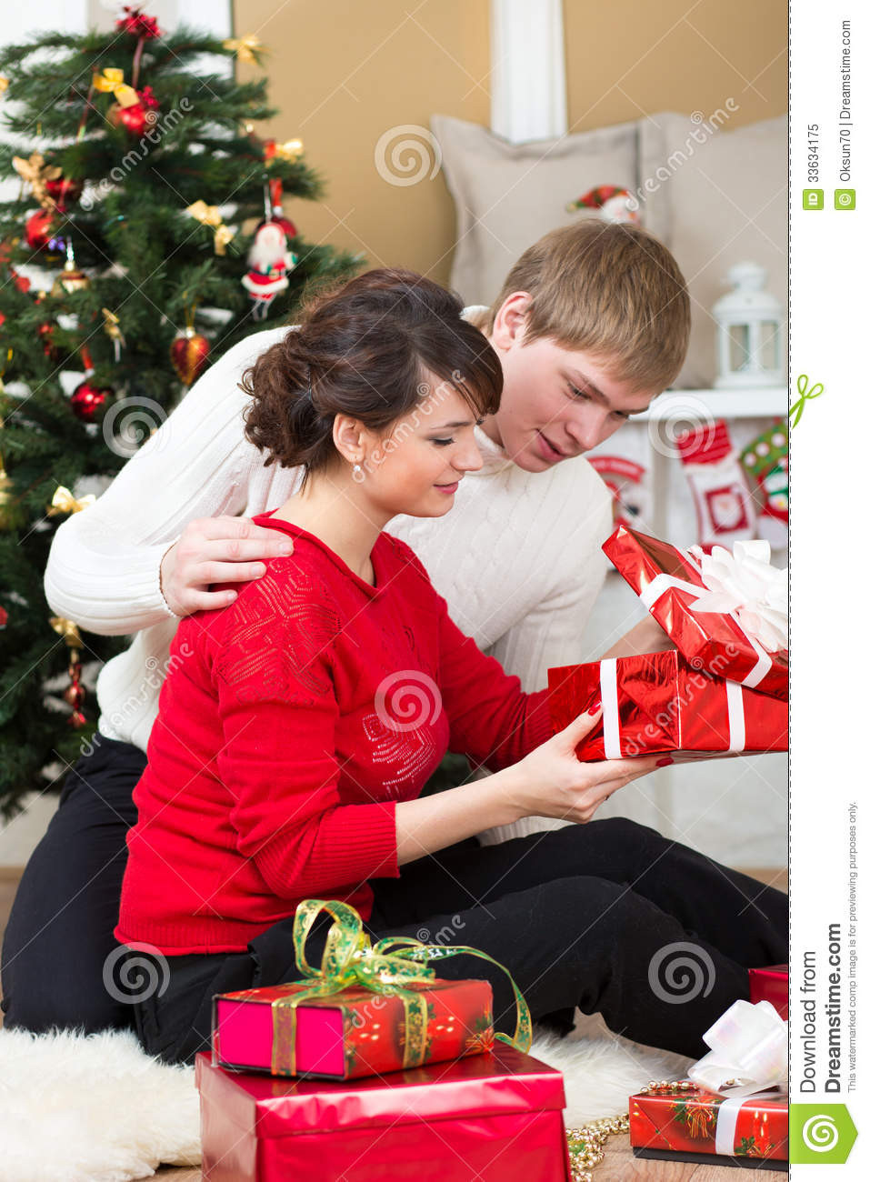 Best ideas about Christmas Gift Ideas For Young Couples . Save or Pin Young Couple With Gifts In Front Christmas Tree Royalty Now.