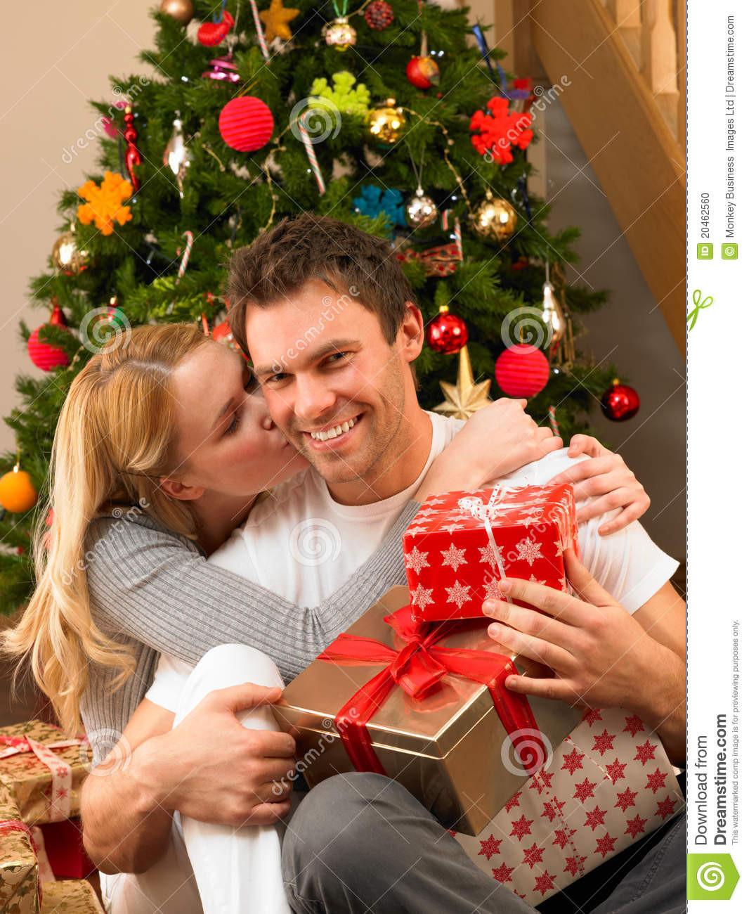 Best ideas about Christmas Gift Ideas For Young Couples . Save or Pin Young Couple With Gifts In Front Christmas Tree Stock Now.